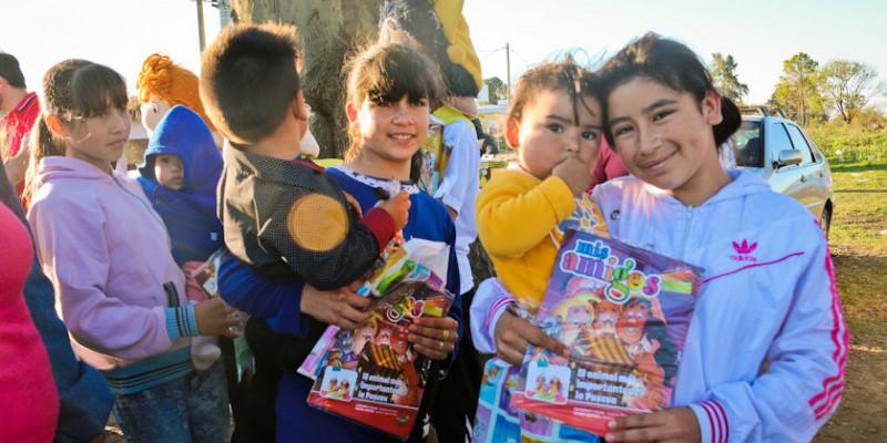 Los niños reciben la revista Mis Amigos.